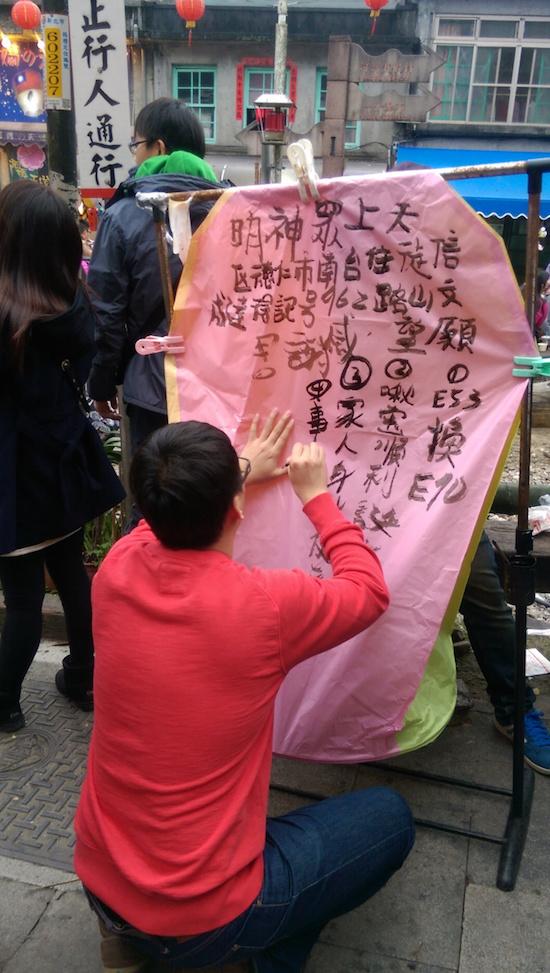 Man decorating his lantern at the Pingxi Lantern Festival