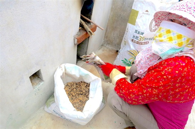 Woman from Nanliao Community in Penghu using peanuts to fuel Fu Ji Stove