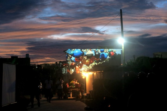 Scenes from Nanliao are projected on a building as night falls