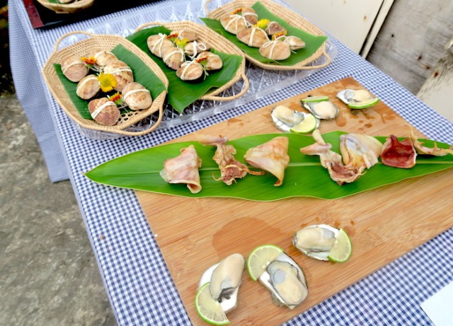 Platters  oysters and dried squid beside a platter of shells filled with rice